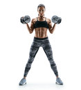 Beautiful young woman in training pumping up muscles of the back and hands with dumbbells. Royalty Free Stock Photo