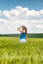 Beautiful young woman turning to smile at the camera as she stands in a scenic green field in the countryside Stock Photo