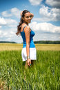 Beautiful young woman turning to smile at the camera as she stands in a scenic green field in the countryside Stock Image