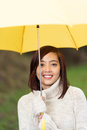 Beautiful young woman under a yellow umbrella asian in warm winter polo neck sweater smiling at the camera Royalty Free Stock Images