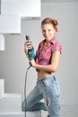 Beautiful young woman uses an electric drill the Royalty Free Stock Image