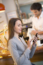 Beautiful young woman using her mobile phone in ba pretty female cell restaurant texting Royalty Free Stock Photography