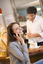 Beautiful young woman using her mobile phone in ba pretty smiling female cell restaurant calling Royalty Free Stock Photography