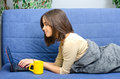 Beautiful young woman using notebook lying on couch drinking coffee while and Stock Photos