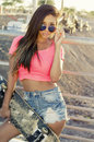 Beautiful young woman walking holding skateboard modern with long hair informal candid portrait Stock Photo
