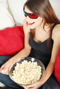 Beautiful young woman watching TV in 3d glasses Royalty Free Stock Image