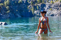 Beautiful young woman wearing a bikini standing in a mountain ri Royalty Free Stock Photo