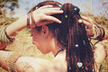 Beautiful young woman wearing dreadlocks hairstyle gathered in a ponytail and decorated assorted beads Royalty Free Stock Photo