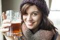 Beautiful young woman wearing knit scarf hat drinking mug beer Royalty Free Stock Photos