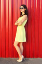Beautiful young woman wearing a sunglasses and yellow dress over colorful red Royalty Free Stock Photo