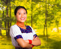 Beautiful young woman wearing traditional andean blouse with necklace, standing posing for camera, arms crossed smiling Royalty Free Stock Photo