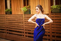 Beautiful young woman wearing a violet dress walking and posing