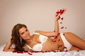 Beautiful young woman wearing white lingerie lying in bed of ros roses on silky sheets with red rose petals Royalty Free Stock Images