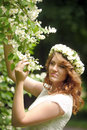 Beautiful young woman wearing a wreath of tiny roses Stock Photo
