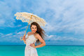 Beautiful young woman in white dress with umbrella on a tropical beach Royalty Free Stock Photo