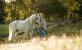 Beautiful young woman with a white horse in the country Stock Photo