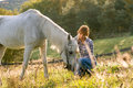 Beautiful young woman with a white horse in the country Royalty Free Stock Photography