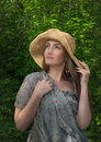 Beautiful young woman in wide hat on green leaf backround Stock Photo