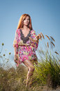 Beautiful young woman in wild flowers field on blue sky background. Portrait of attractive red hair girl with long hair relaxing Royalty Free Stock Photo
