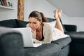 Beautiful young woman working on laptop at home portrait of while lying sofa female using Stock Photo