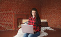 Beautiful young woman working in modern loft home interior. Female using contemporary notebook texting message Royalty Free Stock Photo