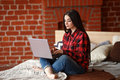 Beautiful young woman working in modern loft home interior. Female using contemporary notebook typing message. Freelance Royalty Free Stock Photo