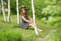 Beautiful young woman in a wreath of flowers near the birch Stock Photo