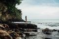 Beautiful young woman in yellow bikini standing on a rock on ocean shore Royalty Free Stock Photo