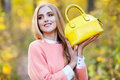 Beautiful young woman with yellow fashionable bag in hands on autumn nature Royalty Free Stock Photo