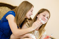 Beautiful young women cute blond sisters or girls friends having fun together in blue and white dress smearing shaving foam two Royalty Free Stock Image