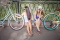 Beautiful young women dressed in elegant dress travel by bicycle Royalty Free Stock Photo