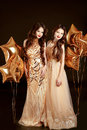 Beautiful young women in elegant golden dress over golden star b Royalty Free Stock Photo