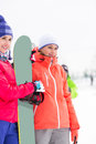 Beautiful young women with snowboard looking away Royalty Free Stock Photo