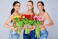 Beautiful young women with tulips a trio of holding bouquets of fresh spring in front of their chests as they smile at the camera Royalty Free Stock Photo