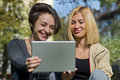 Beautiful young women using tablet outside two Royalty Free Stock Photo