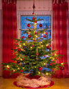 Beautifully decorated xmas tree in the corner of a large luxurious family room Stock Photography