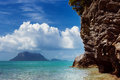 Beautuful tranquil sea scene with cloudy sky and a green cliff Stock Image