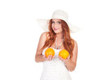 Beautuful woman with red long hair posing in white dress and hat holding two oranges over background Royalty Free Stock Photography