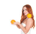 Beautuful woman with red long hair posing in white dress and holding oranges over background Royalty Free Stock Photography