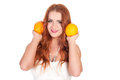 Beautuful woman with red long hair posing in white dress and holding oranges over background Royalty Free Stock Images