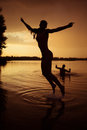 Beauty and the beast slender young girl jump in river at sunset Stock Images