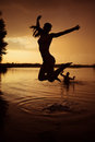 Beauty and the beast slender young girl jump in river at sunset Royalty Free Stock Photo