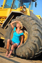 Beauty beautiful woman with blond curls posing on a digger Royalty Free Stock Photos