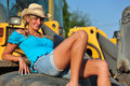 Beauty beautiful woman with blond curls posing on a digger Stock Photo