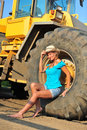 Beauty beautiful woman with blond curls posing on a digger Royalty Free Stock Photography