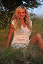 Beauty beautiful woman with blond curls posing on a meadow Royalty Free Stock Photography