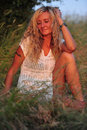Beauty beautiful woman with blond curls posing on a meadow Royalty Free Stock Image