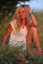 Beauty beautiful woman with blond curls posing on a meadow Royalty Free Stock Photos