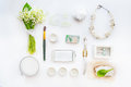Beauty blog concept. Female styled accessories: smartfone, watches, necklace, cosmetic and bouquet of may-lily flowers on white ba Royalty Free Stock Photo