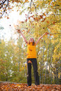 Beauty blond throws leaves in park in autumn Stock Photos